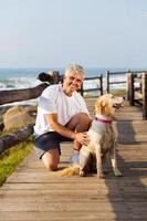 ativo homem sênior e seu cachorro na praia foto