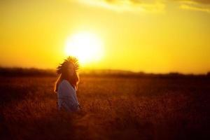 mulher em um campo de trigo ao pôr do sol