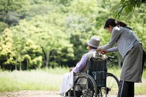 sênior em uma cadeira de rodas e ajudante foto