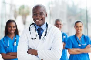 médico americano africano com colegas no fundo