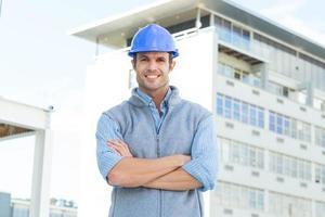 arquiteto masculino em pé braços cruzados fora do edifício
