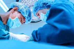 dois cirurgiões veterinários na sala de cirurgia foto