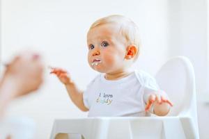 comer manchada adorável menina na cadeira de alimentação pela mãe foto