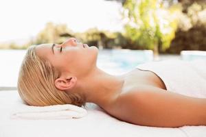 linda mulher deitada na mesa de massagem no centro de bem-estar foto