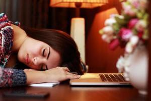 mulher dormindo em cima da mesa foto