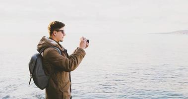 homem viajante tirando fotos na praia na primavera