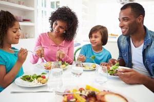 família afro-americana a comer a refeição em casa juntos foto