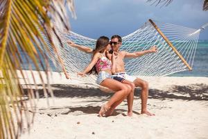 casal romântico relaxante na rede de praia