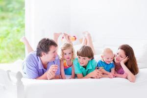 grande e feliz família grande em uma cama foto
