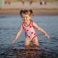 adorável menina brincando com uma água no mar foto