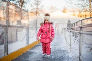 adorável menina feliz desfrutando de patinar na pista de gelo foto
