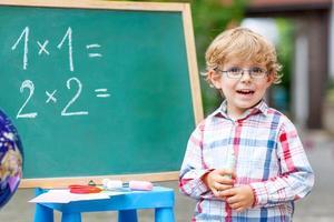 garoto garoto bonitinho com óculos no quadro-negro praticando mathem foto