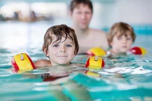 jovem pai ensinando seus dois filhos pequenos a nadar dentro de casa