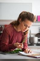 jovem dona de casa estudando especiarias frescas ervas na cozinha
