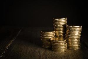 pilhas de moedas de ouro em um fundo escuro natural foto