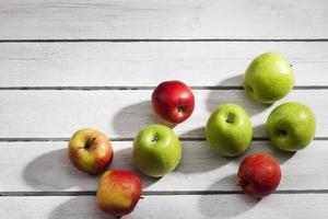 maçãs verdes e vermelhas na mesa de madeira foto