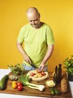 homem de meia idade cozinhar salada fresca foto