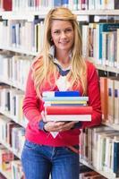 estudante maduro na biblioteca segurando livros foto