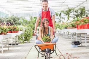 casal de vendedores se divertir empurrando o carrinho de mão em uma estufa foto