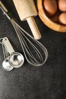 utensílios de cozinha e ingredientes de panificação no fundo preto, cópia-espaço.