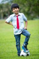 menino asiático com futebol no parque foto