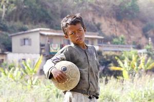 pobreza - menino malgaxe mão segurando uma bola de futebol foto