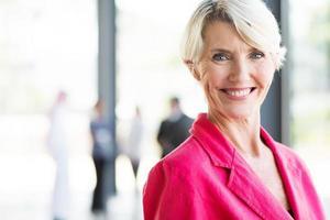 empresária envelhecida média no escritório moderno foto