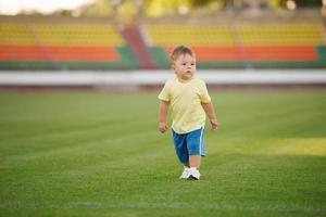 menino engraçado no estádio de futebol foto