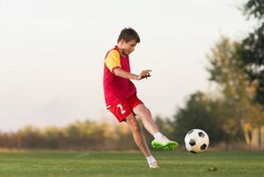 garoto chutando uma bola de futebol foto