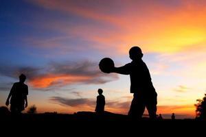 menino de bola de futebol jogando o pôr do sol foto