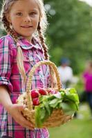 menina segurando cesta com rabanetes vermelhos foto