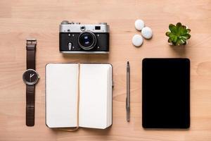 abriu o bloco de notas em branco, caneta, relógio, câmera vintage, tablet e flor foto