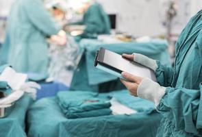 cirurgião usando tablet digital na sala de operação foto