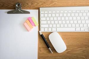 mesa de escritório com prancheta, bloco de notas, teclado de computador e mous foto