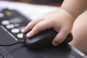 mão do bebê usando o mouse do computador foto