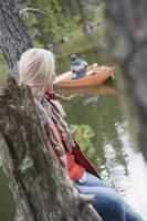 obertauern, mulher sentada no tronco da árvore olhando foto