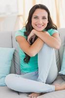 linda morena sentada no sofá foto