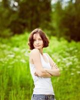 bela jovem sardenta com os braços cruzados no campo de verão foto