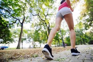 duas belas mulheres correndo no parque foto