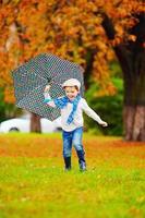 menino feliz, desfrutando de uma chuva de outono no parque foto