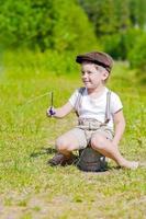 pequeno pescador senta-se com vara de pescar foto