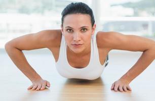 determinada mulher bonita fazendo flexões no ginásio foto
