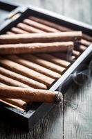 fumaça subindo de um charuto queimando no humidor de madeira foto