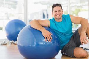 jovem sorridente, sentado com bola de fitness no ginásio foto