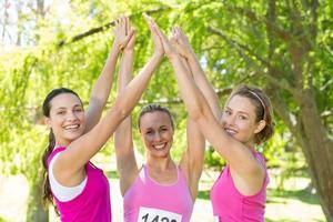 mulheres sorridentes correndo para conscientização do câncer de mama foto