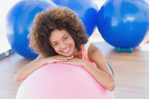 mulher jovem sorridente com bola de fitness no ginásio foto