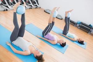 desportivas mulheres segurando bolas entre os tornozelos no estúdio de fitness foto