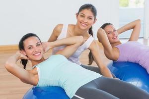 treinador, ajudando a jovem mulher com bola de fitness foto
