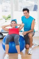 treinador masculino, ajudando a mulher com seus exercícios na academia foto