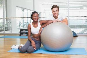 personal trainer e cliente sorrindo para a câmera com bola de exercício foto